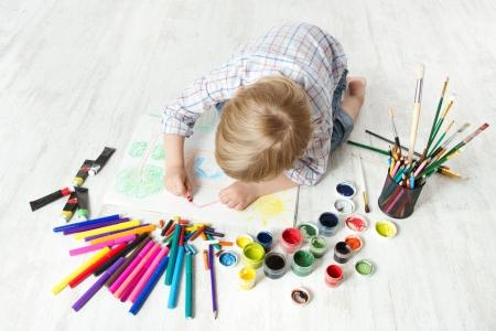 아이가 그림 도구를 많이 사용하여 앨범에 크레용으로 그림을 그리기. 상위 뷰입니다. 창의성 개념입니다.