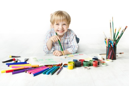 brush in: Happy cheerful child drawing with brush in album using a lot of painting tools. Creativity concept. Stock Photo