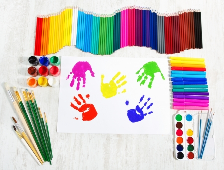 Painting tools set and multicolor child hand prints. Creativity concept. Top view. photo