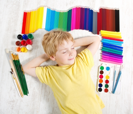 Child dreaming lying next to pencils, brushes and paints.  Creativity and inspiration concept. Top view. photo