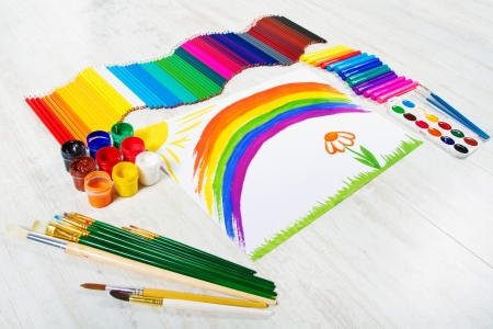 Painting tools set and child drawing picture of rainbow. Creativity concept. photo