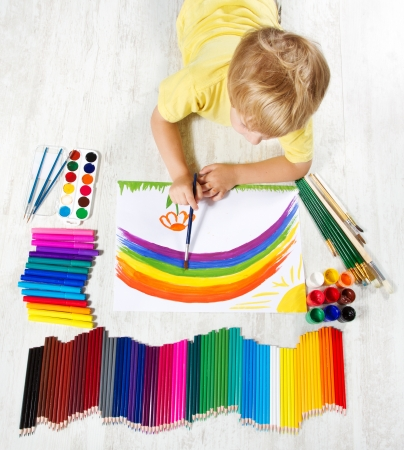 Child painting picture with brush in album using a lot of painting tools. Top view. Creativity concept.   photo