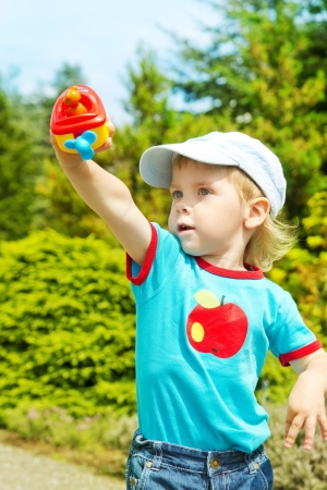Kleiner Junge spielt mit Spielzeug-Flugzeug im Freien