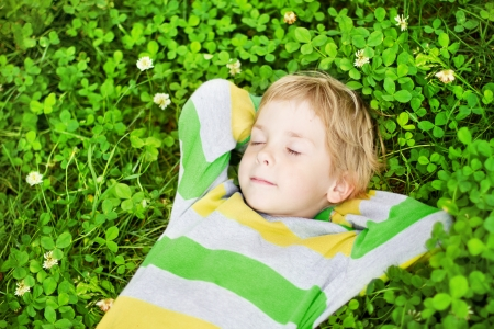 Little child sleeping in clover flower field, hands behind head. High angle view photo