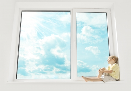 Child sitting on window, enjoying sunshine and dreaming. Big window and sky. photo
