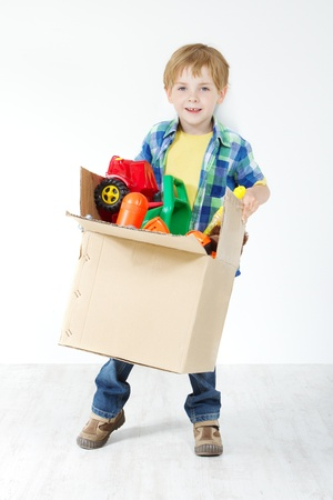 Child holding cardboard box packed with toys. Moving and growing concept photo
