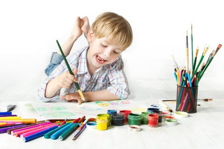 children: Happy cheerful child drawing with brush in album using a lot of painting tools. Creativity concept. Stock Photo