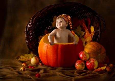Child in cap inside pumpkin. Basket with autumn harvest photo