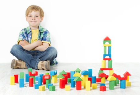 recoger: Muchacho que se sienta al lado de los bloques de construcción y sonriente