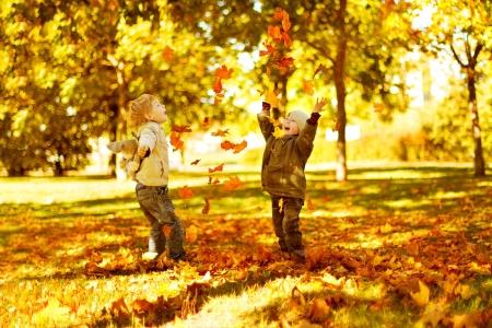 ni�os jugando en el parque: Ni�os jugando con hojas de oto�o caidas en el parque Foto de archivo