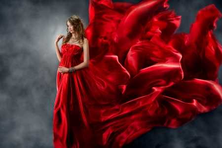 Beautiful woman in red waving silk dress as a flame. Looking down. Stock Photo