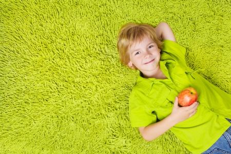 fashion shoot: Child lying on the green carpet background, holding apple. Boy smiling and looking at camera Stock Photo