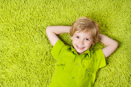 green carpet: Happy child lying on the green carpet background. Boy smiling and looking at camera