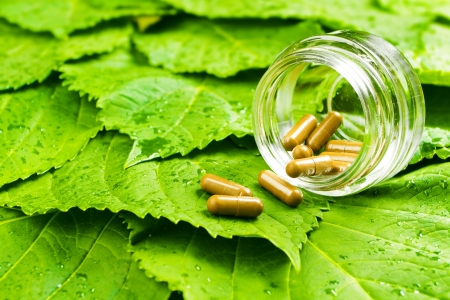 Pills in jar over green leaves  Healthy vitamin concept photo