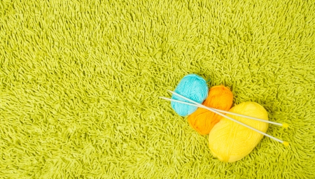 knitting needles: Knitting yarn balls and needles over green carpet background Stock Photo