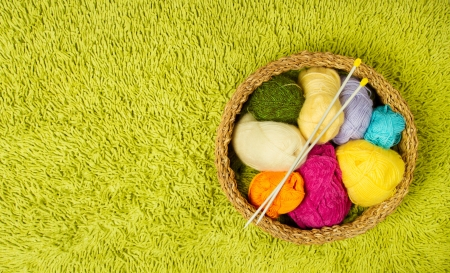 Knitting yarn balls and needles in basket over green carpet background photo