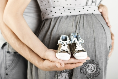 Newborn baby booties in parents hands  Pregnant woman belly
