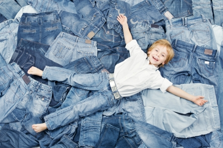 Happy child on jeans background. Denim fashion photo