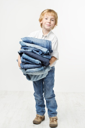 blue jeans kids: Child holding jeans stack. Kids clothing fashion. White background. Stock Photo