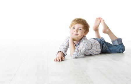 bambini pensierosi: Bambino sdraiato sul pavimento e guardando la fotocamera