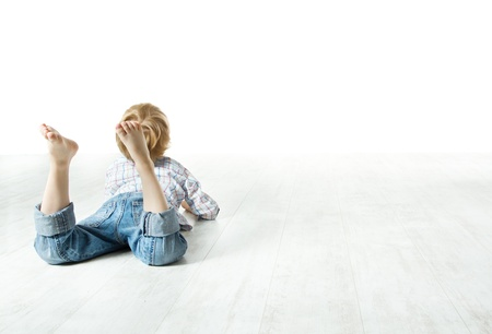 Child  back lying down on floor and looking forward photo