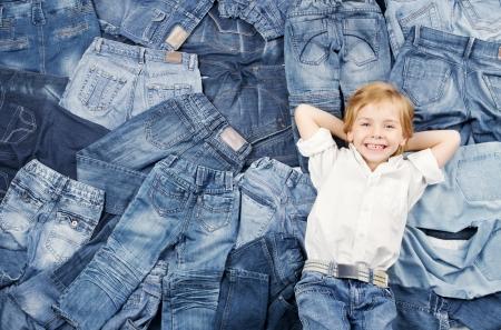 pantalones abajo: Niño feliz en la moda los pantalones vaqueros del dril de algodón de fondo Foto de archivo