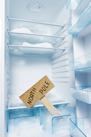 Fridge with frost and North Pole sign  Global warming photo