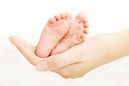 mani e piedi: Gambe bambino in mani della madre