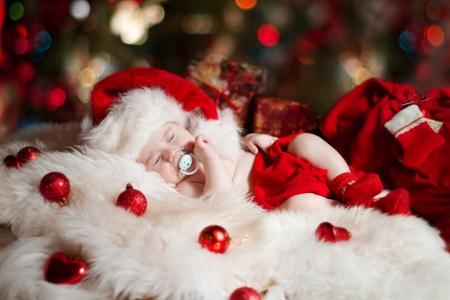 recien nacido: Navidad beb� reci�n nacido que duerme en sombrero de Pap� Noel como regalo de a�o nuevo
