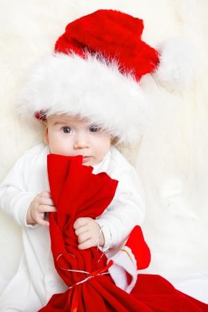 baby kerst: Christmas baby met rode zak in Santa Claus hoed Stockfoto