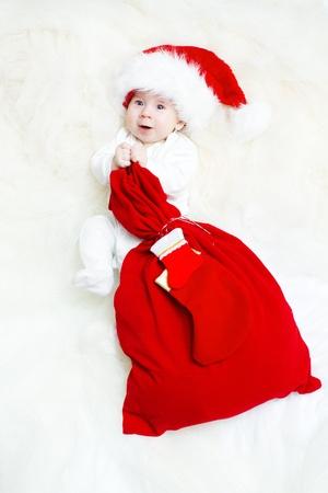 baby kerst: Christmas baby het dragen van Santa Claus hoed met rode geschenk tas met sok