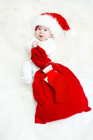 Christmas baby wearing Santa Claus hat holding red gift bag with sock