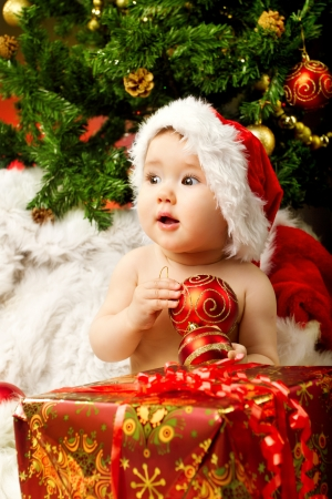 Christmas baby in hat holding red ball near gift box and new year fir tree