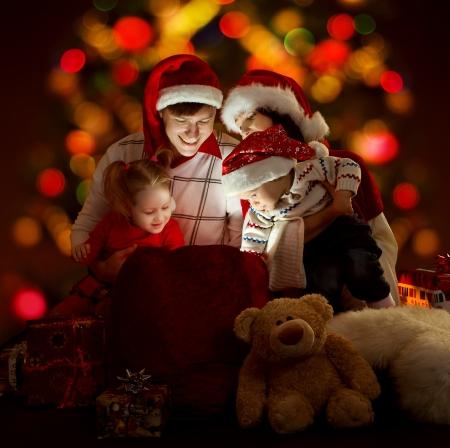 pere noel: Happy famille de quatre personnes dans des chapeaux rouges ouvert le sac d'�clairage avec des cadeaux Banque d'images
