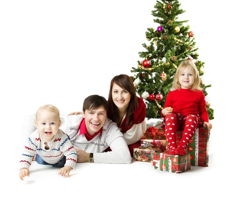 family celebration: Christmas family of four persons and fir tree with gift boxes