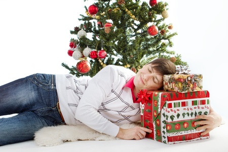 Christmas gift  Smiling happy man lying and sleeping front of fir tree and holding present box photo