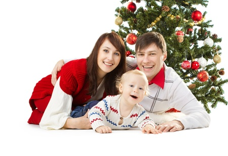 Christmas family of three persons and fir tree, smiling happy parents and child photo