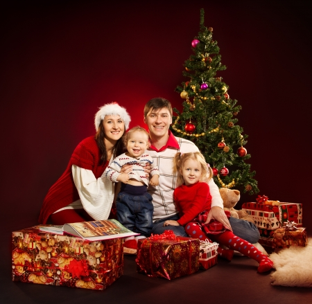baby kerst: Kerst gezin van vier personen en spar met cadeau dozen op rode achtergrond Stockfoto