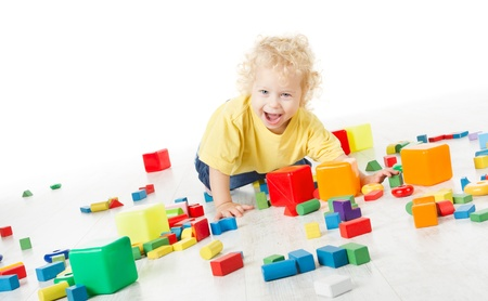 Child happy playing blocks over white photo