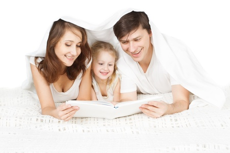 Happy family: parents reading book with child in bed Stock Photo - 16392727