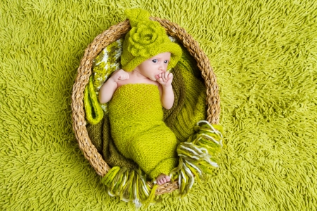 Newborn baby in woolen hat inside basket over green background photo