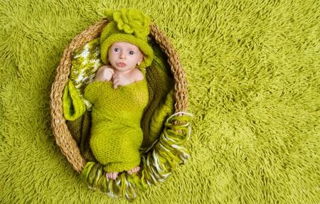 woolen: Newborn baby in woolen hat inside basket over green background