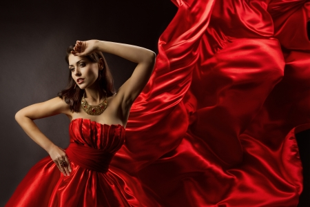 wind dress: Woman in red dress dancing with flying fabric