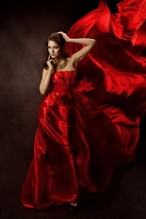 Frau im roten Kleid mit fliegenden Stoff
