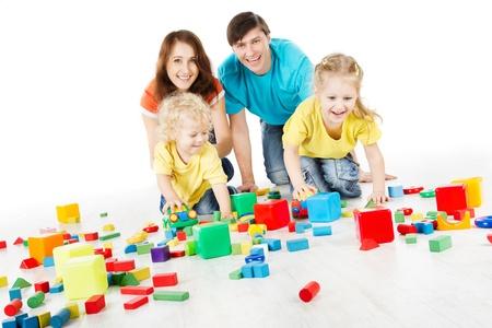 padres e hijos felices: Familia feliz. Padres con tres niños jugando bloques de más de blanco Foto de archivo