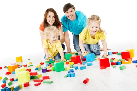 two parents: Happy family. Parents with three kids playing blocks over white