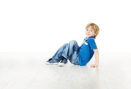 Smiling little boy sitting down on floor and looking at camera Stock Photo - 16660423