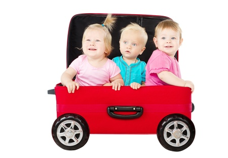 Group of kids driving in suitcase car. Shipping and innovation concept. Isolated white photo