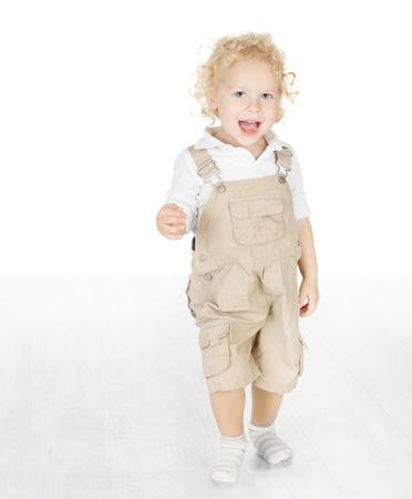 Happy child smiling, standing on white floor photo