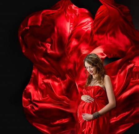 traje de gala: Mujer embarazada en vestido de noche rojo volando en el viento